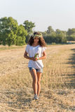 Teen girl in a wreath of daisies walketh in  field Royalty Free Stock Photo
