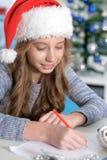 Teen girl writing letter. Portrait of teen girl in Santa hat writing letter Royalty Free Stock Image