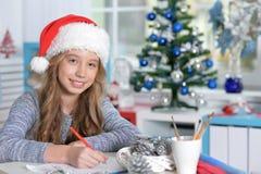Teen girl writing letter. Portrait of teen girl in Santa hat writing letter Stock Photo