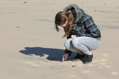 Teen girl writing in sand Stock Photos