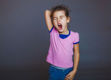 Teen girl yawns sleepy opened her mouth on gray Royalty Free Stock Photography