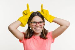 Teen girl in yellow protective gloves. White background, cleaning time. A teen girl in yellow protective gloves. White background, cleaning time Royalty Free Stock Photos