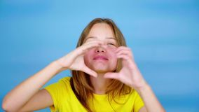 Teen girl in a yellow t-shirt is looking at camera, blows a kiss and showing heart shape
