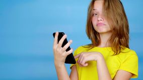 Teen girl in a yellow t-shirt is swipe on smartphone, surprised and says wow