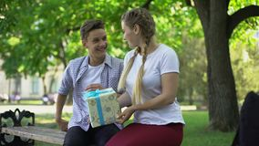 Teen girlfriend presenting birthday box to boyfriend in park, surprise present. Stock footage stock footage