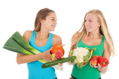 Teen girlfriends with fresh vegetables and fruit. Teen girlfriends with many healthy vegetables and fresh fruit isolated over white background Royalty Free Stock Photo