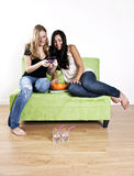 Teen girlfriends hanging out. Two teenage girlfriends  sharing a phone sending a text message on a couch Royalty Free Stock Photo
