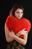 Teen girll with heart pillow Stock Images