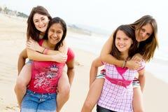 Teen girls. Piggyback on beach Royalty Free Stock Image
