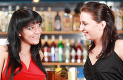 Teen girls at bar. Portraits of two teenage girls socializing together at a bar stock photo