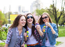 Teen girls blowing soap bubbles. Young happy teenagers having fun in summer park. Royalty Free Stock Images