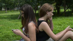 Teen girls with cellphones in the park stock video footage