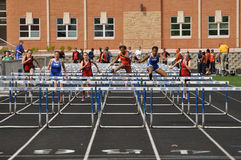 Teen Girls Competing in High School Hurdles Race Royalty Free Stock Image
