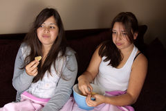 Teen girls eating junk food. Two twin brunette hispanic sisters sitting on the sofa at home wearing pajamas sharing a bowl of potato chips royalty free stock photo