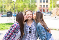 Teen girls enjoy friendship. Young happy teenagers having fun in summer park. Stock Photos