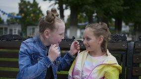 Teen girls consider earrings in each other`s ears sitting on bench in city park. Teen girls friends are looking at jewelry in the ears. Girls consider earrings stock footage