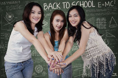 Teen girls gathering hands in class Royalty Free Stock Photos