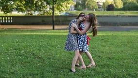 Teen girls girlfriend met in Park and happily hug. Shot in full growth. stock footage