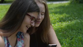 Teen girls having fun with cell outdoor stock video footage