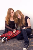 Teen girls huddling together. Two teen girls huddling together against a building, as if one is in emotional pain Royalty Free Stock Photos