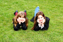 Teen girls laying on the green grass royalty free stock photos