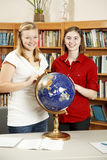 Teen Girls in Library with Globe Royalty Free Stock Photography