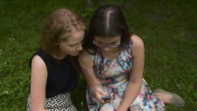 Teen girls listening to music with cellphone stock footage