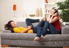 Teen girls listening to music on couch stock photography