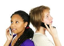 Teen girls with mobile phones. Isolated portrait of two teenage girls with cell phones Stock Photography