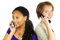 Teen girls with mobile phones. Isolated portrait of two teenage girls with cell phones Royalty Free Stock Photos