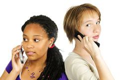 Teen girls with mobile phones. Isolated portrait of two teenage girls with cell phones Royalty Free Stock Photo