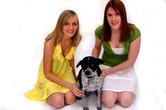 Teen girls with pet dog. Two pretty smiling teen girls with a pet dog on a white background Stock Image