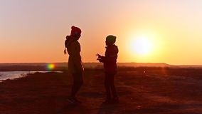 Teen girls with phone listening to music on headphones against the sunset, girls with headphones dancing to music. stock footage