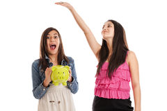 Teen girls with piggy bank Royalty Free Stock Photo