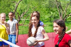 Teen girls playing volleyball together on ground Stock Photos