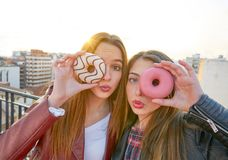 Teen girls portrait with donuts in eye having fun Royalty Free Stock Photos