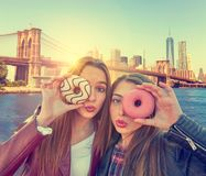 Teen girls portrait with donuts in eye New York stock photography