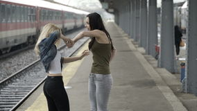 Teen girls reunited meeting in train station taking photo selfie with smartphone and having fun before summer trip. Happy teen girls reunited meeting in train stock video footage