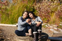 Teen girls on rock using smartphone by lake in autumn Stock Image