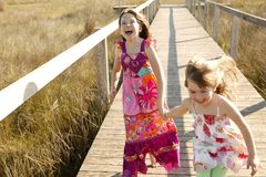 Teen girls running outdoor at the park. Teen two girls running outdoor at the park, hippy pink dress Royalty Free Stock Photo