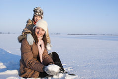 Teen girls sitting in snow. And playing Royalty Free Stock Photography