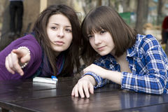 teen girls sitting in street cafe showing  at som Royalty Free Stock Image