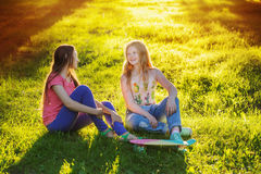 Teen girls with with skateboard in summer park Stock Photo