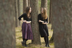 Teen girls standing in a forest near a tree talking to each other. Nature. Royalty Free Stock Photo