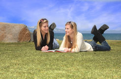 Teen girls studying. Two pretty teen aged girls laying on grass in front of a lake, studing from a book Stock Photography