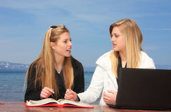 Teen Girls Studying. Two teen aged girl students sitting at a park bench studying with a book and computer Stock Images