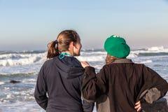 Teen Girls Talk Beach Waves. Teen girls social relax laugh talk-time at beach watching ocean waves early morning holidays Stock Photos