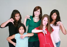 Teen girls with thumbs down. Diverse group of unhappy girls with thumbs down Royalty Free Stock Image