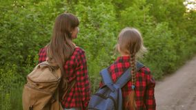 Teen girls travel with backpacks hand in hand. tourists children go along the country road. Happy family traveling on stock video