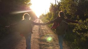 Teen girls travel and hold hands. children travelers. Hiker Girl. happy girls travelers with backpacks run along country stock video footage